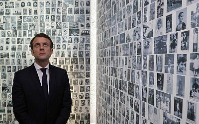 In this photo from April 30, 2017, Emmanuel Macron looks at some of the 2,500 photographs of young Jews deported from France, during a visit to the Shoah memorial in Paris, France. (Philippe Wojazer/Pool Photo via AP, File)