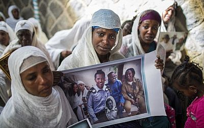 In this Wednesday, February 28, 2018 file photo, Snteayw Girmaw holds a photo of her sister Zemenech Bililin, wearing Israeli military uniform, during a solidarity event at the synagogue in Addis Ababa, Ethiopia. (AP Photo/Mulugeta Ayene, File)