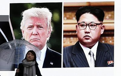 A woman walks by a huge screen showing US President Donald Trump, left, and North Korea's leader Kim Jong Un, in Tokyo, Friday, March 9, 2018. (AP Photo/Koji Sasahara)