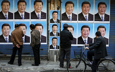 In this March 26, 2016 photo, people look at a building covered in posters of Chinese President Xi Jinping in Shanghai. (Chinatopix via AP)