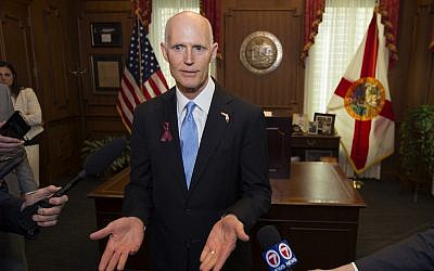 Florida Governor Rick Scott talks to the media in his office after signing the Marjory Stoneman Douglas Public Safety Act at the Florida Capital in Tallahassee, Florida, on March 9, 2018. (AP Photo/Mark Wallheiser)