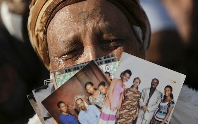 An Ethiopian Israeli woman holds pictures of relatives as she protests in front of the Knesset in Jerusalem, Monday, March 12, 2018. (AP Photo/Sebastian Scheiner)