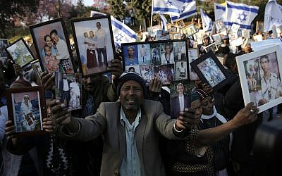 Ethiopian Israelis hold pictures of relatives as they protest in front of the Knesset in Jerusalem, March 12, 2018. (AP Photo/ Sebastian Scheiner)