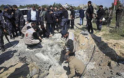 Hamas personnel inspect the site of an explosion that occurred as the convoy of Palestinian Authority Prime Minister Rami Hamdallah entered Gaza through the Erez crossing with Israel, on the main road in Beit Hanoun, Gaza Strip, on March 13, 2018. (AP Photo/Adel Hana)