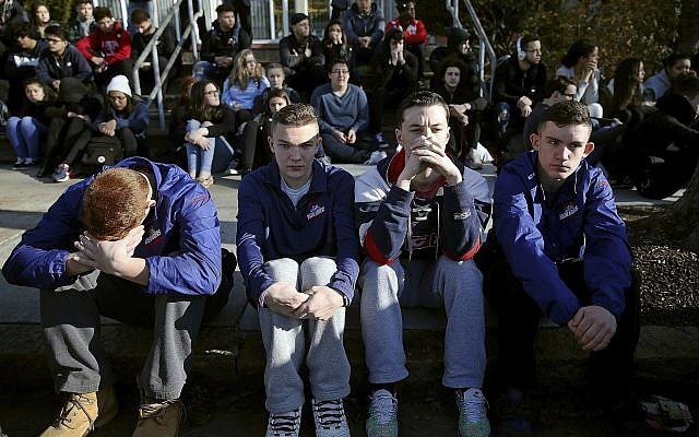 In this February 28, 2018, file photo, Somerville High School students sit on the sidewalk on Highland Avenue during a student walkout at the school in Somerville, Massachusetts. (Craig F. Walker/The Boston Globe via AP, File)