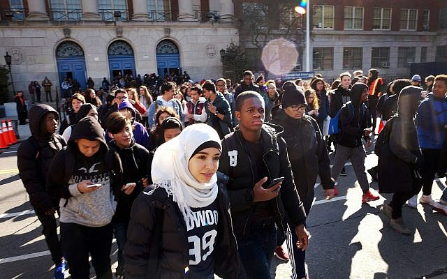 Hundreds of students walk out of Midwood High School as part of a nationwide protest against gun violence March 14, 2018, in the Brooklyn borough of New York. (AP Photo/Mark Lennihan)