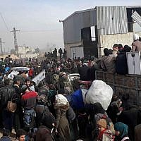 This photo released by the Syrian official news agency SANA, shows Syrian civilians with their belongings as they flee from fighting between the Syrian government forces and rebels, in Hamouria in eastern Ghouta, a suburb of Damascus, Syria, Thursday, March. 15, 2018. (SANA via AP)