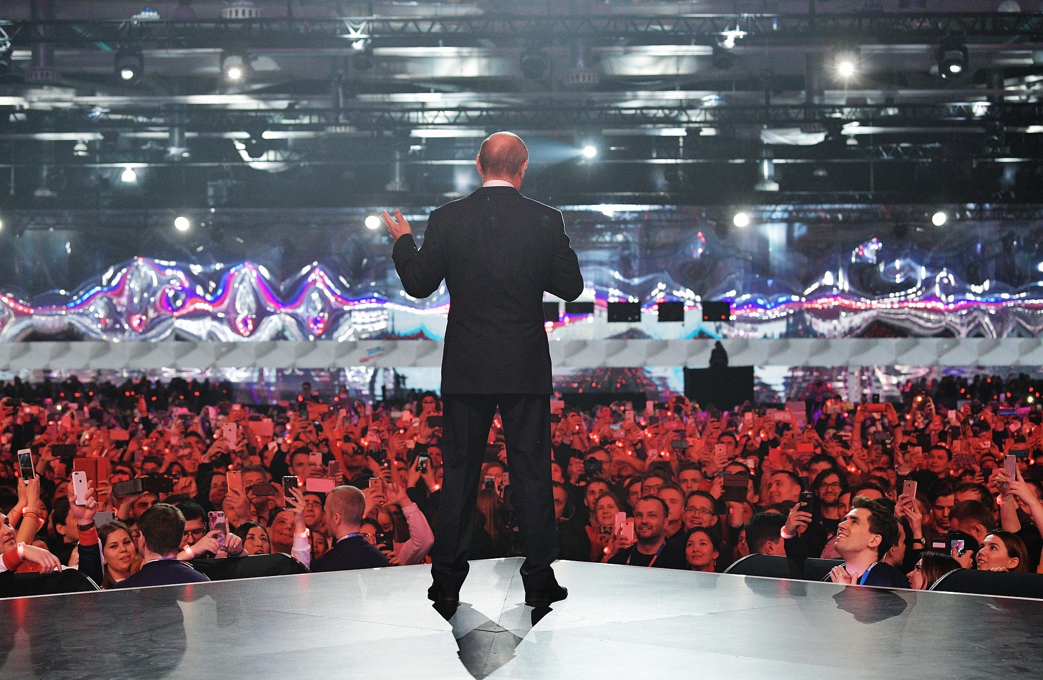 Russian President Vladimir Putin gestures while speaking at a youth forum