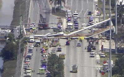 In this frame from video, emergency personnel work at the scene of a collapsed bridge in the Miami area, March 15, 2018. (WPLG-TV via AP)