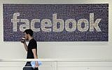 In this March 15, 2013, file photo, a Facebook employee walks past a sign at Facebook headquarters in Menlo Park, Calif.  (AP Photo/Jeff Chiu)