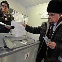 Two men cast their ballots at a polling station in Yelizovo, about 30 kilometers ( 19 miles) north-east from Petropavlovsk-Kamchatsky, capital of Kamchatka Peninsula region, Russian Far East, Russia, on Sunday, March. 18, 2018. (AP Photo/Alexander Petpov)