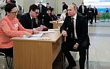 Russian President and presidential candidate Vladimir Putin waits to get his ballot as he arrives to vote at a polling station, during Russia's presidential election in Moscow, Russia, March 18, 2018. (Mikhail Klimentyev, Sputnik, Kremlin Pool Photo via AP)