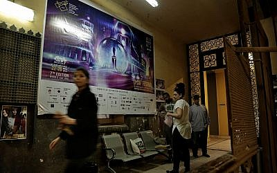 In this March 14, 2018 photo, staff working for the Downtown Contemporary Arts Festival walk outside their office in Cairo. (AP Photo/Nariman El-Mofty)