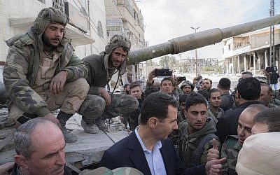 In this photo released on the official Facebook page of the Syrian Presidency, Syrian President Bashar Assad, center, speaks with Syrian troops during his visit to the front line in the newly captured areas of eastern Ghouta, near the capital Damascus, Syria, Sunday, March 18, 2018. (Syrian Presidency Facebook Page via AP)