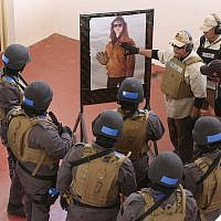 In this Sunday, March 18, 2018 photo, an instructor speaks to members of a Tunisian police commando unit during a drill at the Jordan Gendarmerie Training Academy, in al-Swaqa, about 44 miles (70 km) south of Amman, Jordan. (AP Photo/Raad Adayleh)