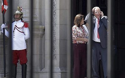 Peru's President Pedro Pablo Kuczynski talks on his cellphone as he leaves the Government Palace also known as the House of Pizarro, in Lima, Peru, Wednesday, March 21, 2018. (AP/Martin Mejia)
