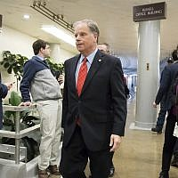 "Sen. Doug Jones, an Alabama Democrat, heads to the Senate to vote on the bipartisan ""Stop Enabling Sex Traffickers Act"" which would allow victims of sex trafficking to sue websites that enabled their abuse, on Capitol Hill in Washington, Wednesday, March 21, 2018. (AP Photo/J. Scott Applewhite)"