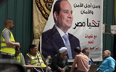 "People chat and smoke under an election campaign banner for Egyptian President Abdel-Fattah el-Sissi that reads, ""For the sake of the nation's security,"" in Cairo, Egypt, March 24, 2018. (AP Photo/Amr Nabil)"
