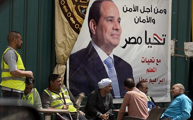 """People chat and smoke under an election campaign banner for Egyptian President Abdel-Fattah el-Sissi that reads, """"For the sake of the nation's security,"""" in Cairo, Egypt, March 24, 2018. (AP Photo/Amr Nabil)"""