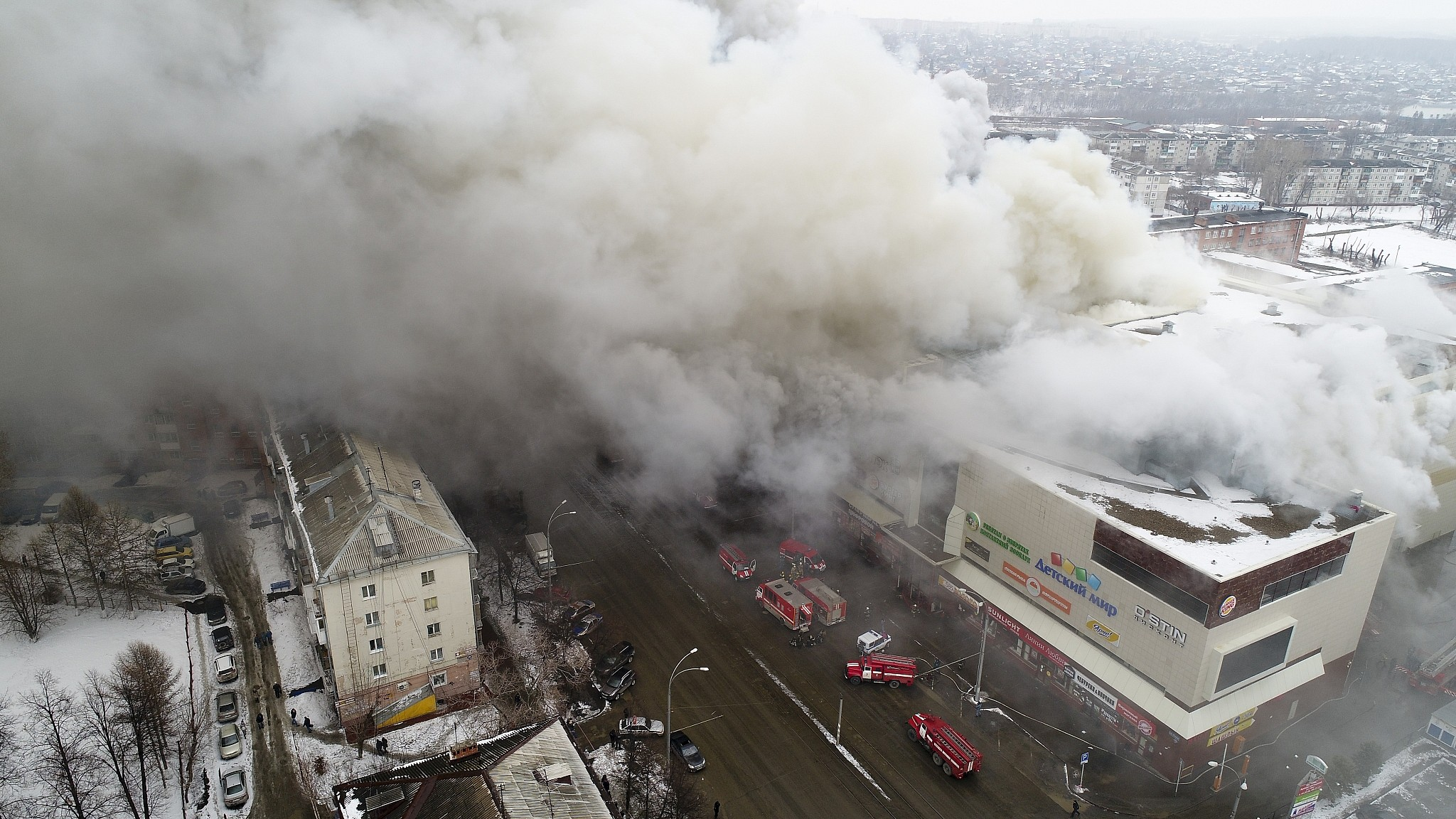 Smoke Rises Above A Multi Story Shopping Center In The Siberian City Of Kemerovo