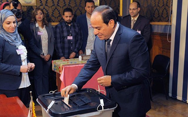 In this photo provided by Egypt's state news agency, MENA, Egyptian President Abdel-Fattah el-Sissi votes in Cairo, Egypt, March 27, 2018. (MENA via AP)