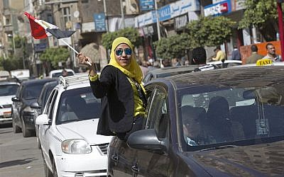 A woman waves an Egyptian national flag as she hangs out a car window outside a polling station in Cairo, Egypt, Monday, March 26, 2018. (AP Photo/Amr Nabil)