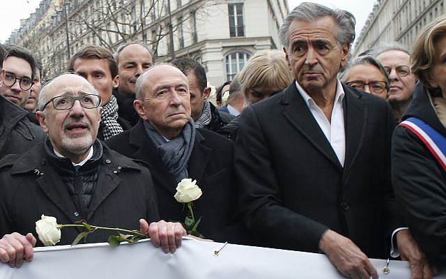 CRIF President (Representative Council of Jewish Institutions in France) Francis Kalifat, left, French interior minister Gerard Collomb, center, and French philosopher and author Bernard-Henri Levy attend a silent march to honor an 85-year-old woman who escaped the Nazis 76 years ago but was stabbed to death last week in her Paris apartment, apparently targeted because she was Jewish, and to denounce racism, in Paris, France, March 28, 2018. (AP Photo/Thibault Camus)