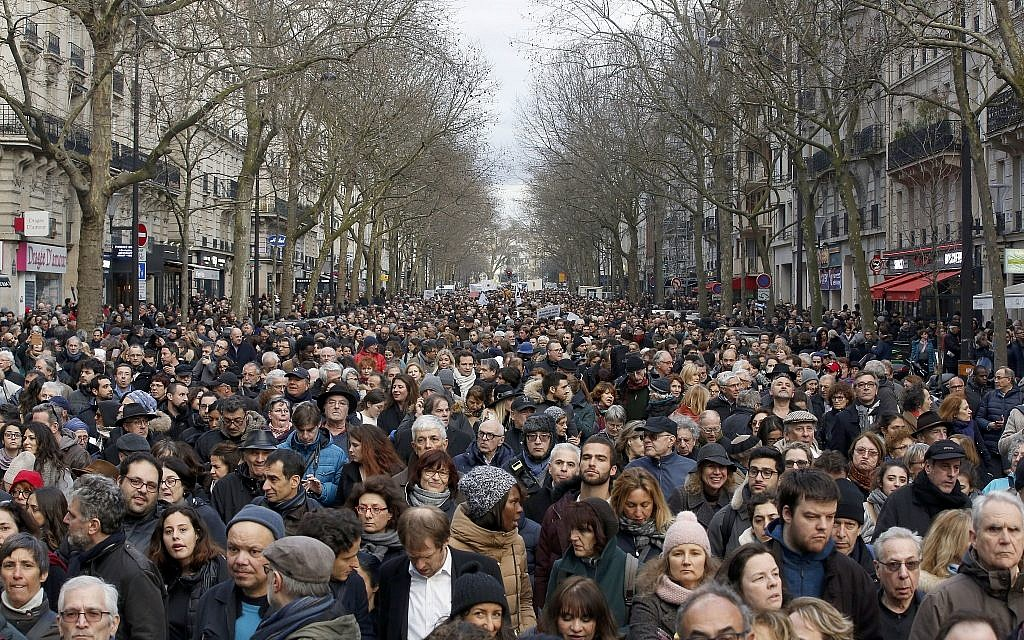 People attend a silent march to honor an 85-year-old woman who escaped the Nazis 76 years ago but was stabbed to death last week in her Paris apartment, apparently targeted because she was Jewish, and to denounce racism, in Paris, France on, March 28, 2018. (AP Photo/Thibault Camus)