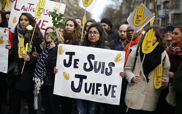 "A woman carries a poster reading ""I am a jew"" as she attends a silent march to honor an 85-year-old woman who escaped the Nazis 76 years ago but was stabbed to death last week in her Paris apartment, apparently targeted because she was Jewish, and to denounce racism, in Paris, France, March 28, 2018. (AP Photo/Thibault Camus)"