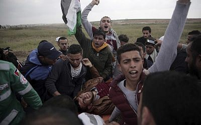 Palestinians chant slogans as they attend a demonstration near the Gaza Strip border with Israel, in eastern Gaza City, Friday, March 30, 2018. (AP Photo/Khalil Hamra)