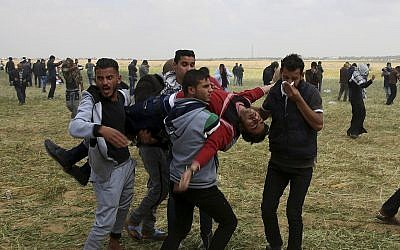 Illustrative image of Palestinian protesters evacuating a wounded youth during clashes with Israeli troops along the Gaza Strip border with Israel, east of Khan Younis, March 30, 2018. (AP Photo/Adel Hana)
