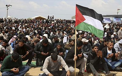 Palestinian protesters pray during a demonstration against Israel along the Gaza Strip border east of Khan Younis, Friday, March 30, 2018. (AP Photo/Adel Hana)