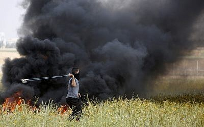 A Palestinian protester slings stones towards Israeli soldiers during clashes with Israeli troops along the Gaza Strip border with Israel, east of Khan Younis, Gaza Strip, Friday, March 30, 2018. (AP/Adel Hana)