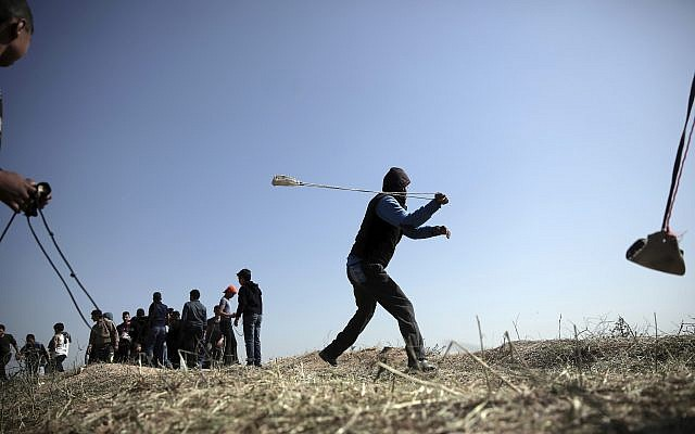 Palestinians hurl stones toward Israeli soldiers during a protest near the Gaza Strip border with Israel, in eastern Gaza City, March 31, 2018. (AP/ Khalil Hamra)