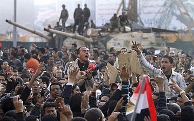 Egyptians protest in front of an army tank in central Cairo, Egypt, Jan. 29, 2011. (AP Photo/Ahmed Ali)