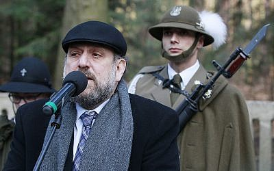 Chief Rabi of Poland, Michael Schudrich, says prayers for the dead at a cemetery where eight Jews killed by the Germans in 1944 were buried, along with the Polish Ulma family that was sheltering them, in Jagiella, Poland, on Thursday, March 17, 2016 during ceremonies honoring the Ulmas and hundreds of Poles who lost their lives trying to save Jews in the Holocaust. (AP Photo/Czarek Sokolowski)
