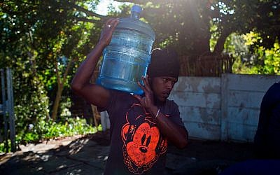 A man carries water at a source for natural spring water in Cape Town, February 1, 2018. (AP Photo/Bram Janssen)