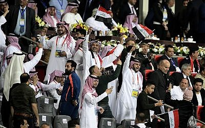 Iraqi and Saudi soccer fans cheer, waving national flags during a friendly soccer match between Iraq and Saudi Arabia in Basra, 550 kilometers (340 miles) southeast of Baghdad, Iraq, Wednesday, Feb. 28, 2018. (AP Photo/Nabil al-Jurani)