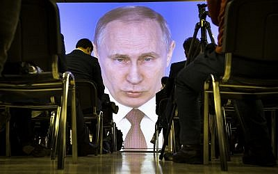 Journalists watch as Russian President Vladimir Putin gives his annual state of the nation address in Manezh in Moscow, Russia, Thursday, March 1, 2018. (AP Photo/Alexander Zemlianichenko)