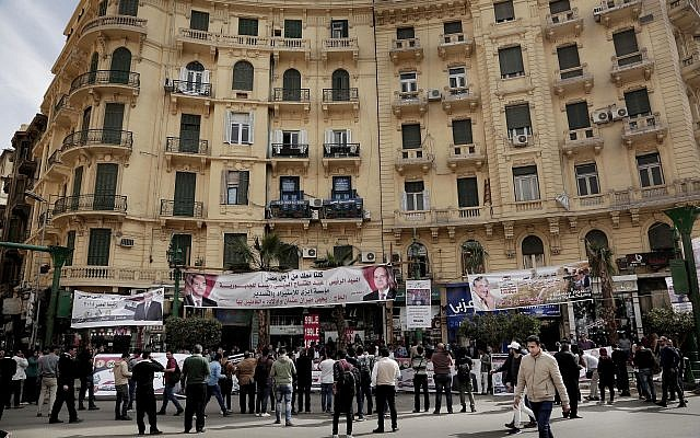 People hold banners of Egyptian presidential candidate Moussa Mustafa Moussa on a street in downtown Cairo, Egypt, Sunday, March 4, 2018. (AP Photo/Nariman El-Mofty)