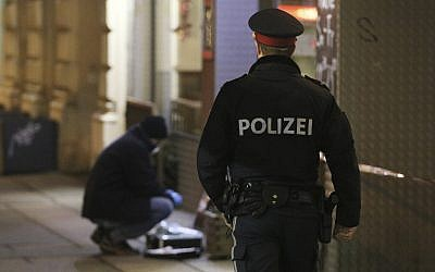 Illustrative: A police officer passes by a forensic expert after several people were injured in a knife attack in Vienna, Austria on March 7, 2018. (AP Photo/Ronald Zak)
