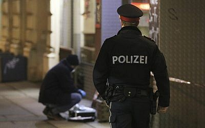 A police officer passes by a forensic expert after several people were reported injured in a knife attack on the streets of Vienna, Austria, on March 7, 2018. (AP Photo/Ronald Zak)