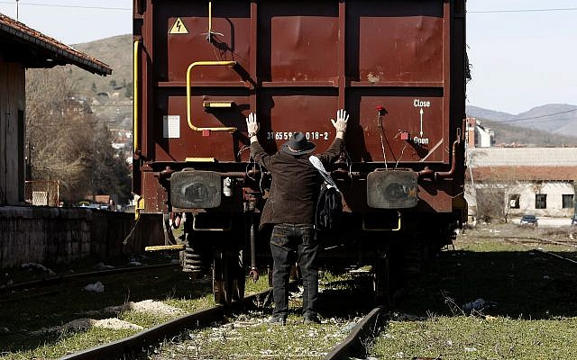 A Jew puts his arms on a freight wagon, during a commemoration for the victims of the Holocaust at the railway station in Bitola, southern Macedonia, on March 11, 2018. (AP Photo/Boris Grdanoski)