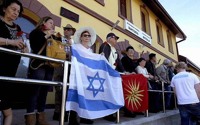 People hold the Israeli and former Macedonian flag as they take part in a commemoration for the victims of the Holocaust, at the railway station in Bitola, southern Macedonia, March 11, 2018. (AP Photo/Boris Grdanoski)