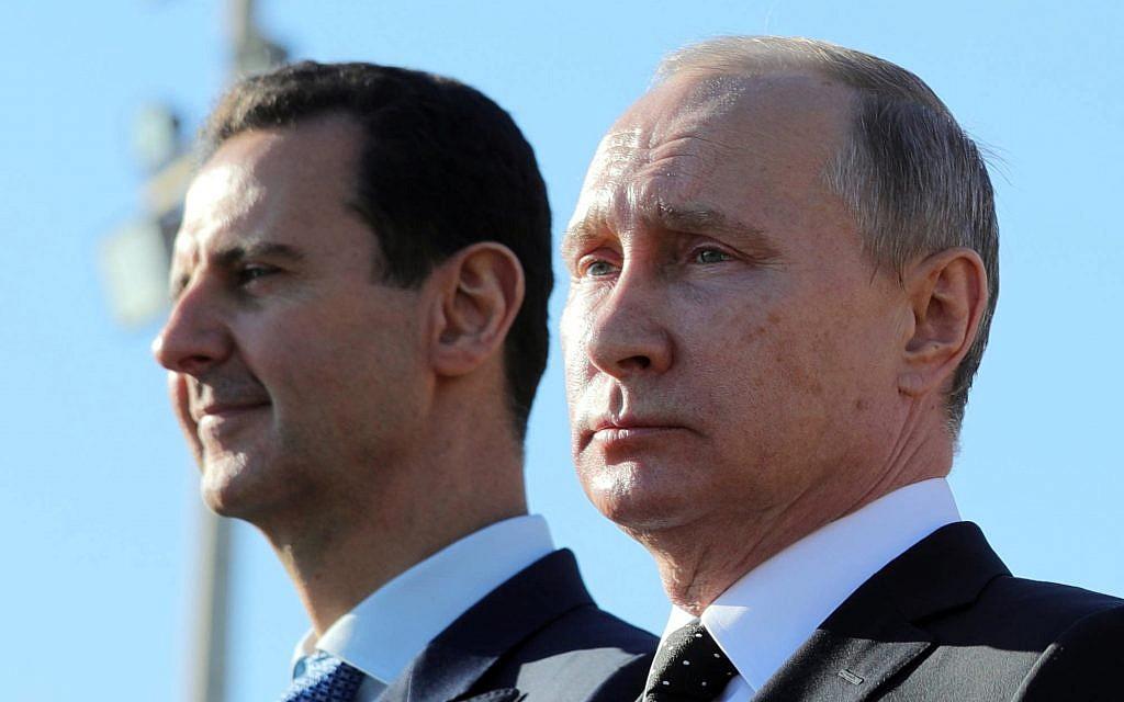 This December 11, 2017 photo shows Russian President Vladimir Putin, right, and Syrian President Bashar Assad watching troops march at the Hemeimeem air base in Syria. (Mikhail Klimentyev, Sputnik, Kremlin Pool Photo via AP)