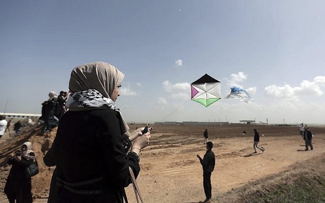 Palestinian protesters fly kites during a demonstration near the Gaza Strip border with Israel, in eastern Gaza City, March 29, 2018. (AP Photo/ Khalil Hamra)