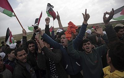 Palestinians chant slogans as they protest against Israel near the Gaza Strip border, in eastern Gaza City, Friday, March 30, 2018. (AP Photo/Khalil Hamra)