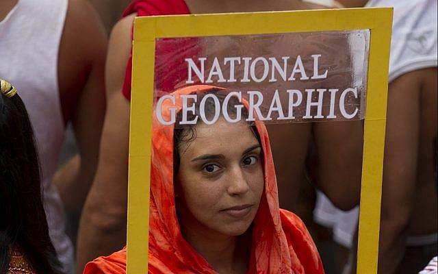 "A reveler holds a frame depicting a front page of National Geographic magazine during ""Ceu na Terra"" block carnival parade in Rio de Janeiro, Brazil, Saturday, February 9, 2013. (AP Photo/Silvia Izquierdo)"