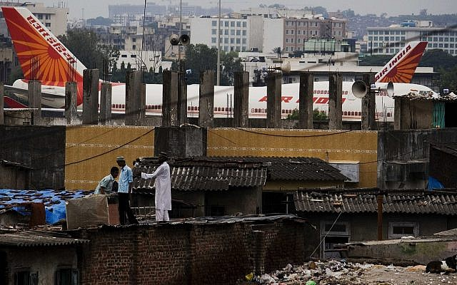 In this Sept. 28, 2009 file photo, Air India passenger jets are parked in the background of slums adjoining the international airport in Mumbai, India.(AP Photo/Dhiraj Singh)