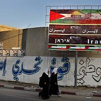 "Palestinian school girls pass a billboard covered by national and Iranian flags with Arabic reading, ""thanks and gratitude to Iran"", in Gaza City, Wednesday, November 28, 2012. (AP/Adel Hana)"
